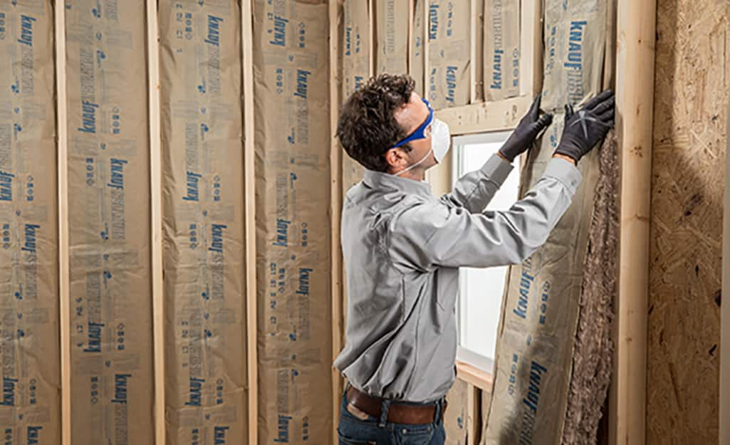 A person installing insulation batts.
