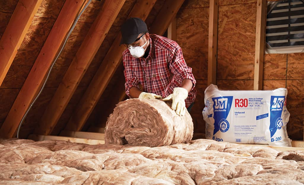 A person installing rolled insulation in an attic.