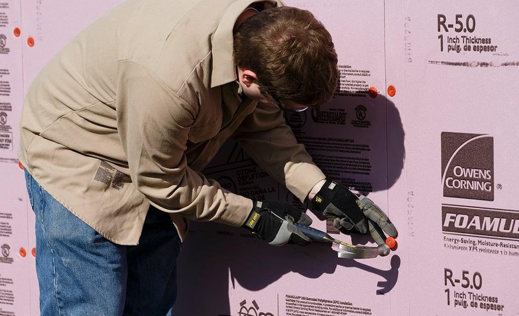 A person installing foam board insulation.