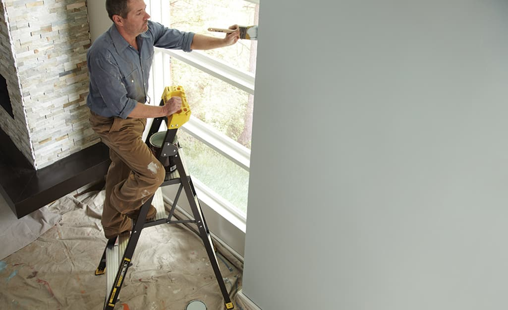 Man standing on a ladder to paint.