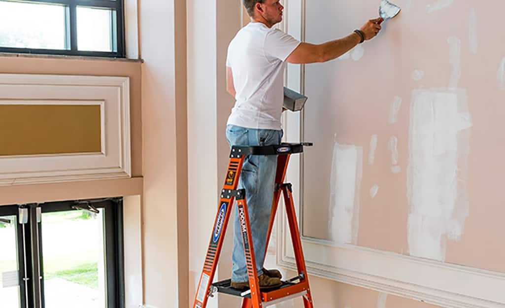 A man patching a wall while standing safely on a platform ladder.