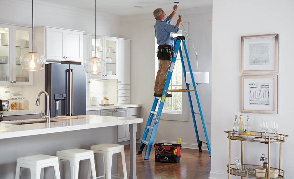 A man standing on a step ladder to paint a kitchen ceiling.