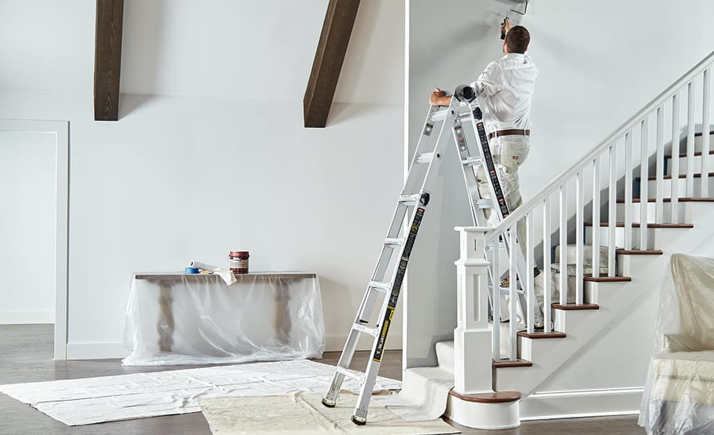 A man standing on a multi-position ladder placed on stairs.