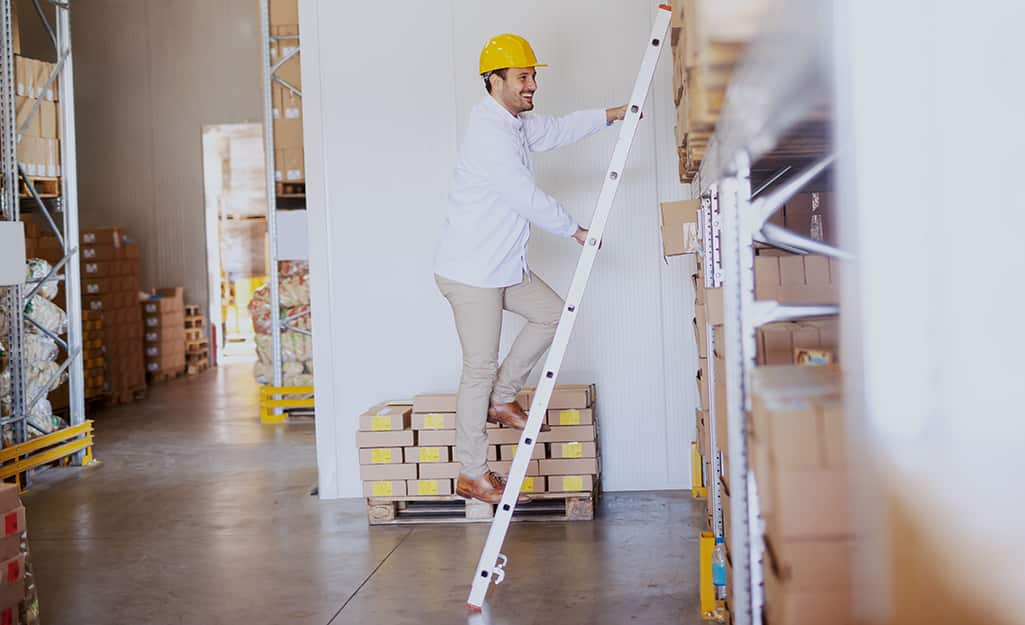 A man climbing a straight ladder leaned against shelves in a warehouse.