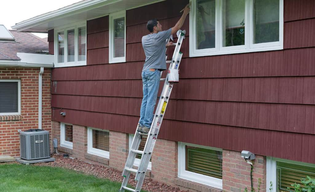 A man on an extension ladder leaned up against a house.