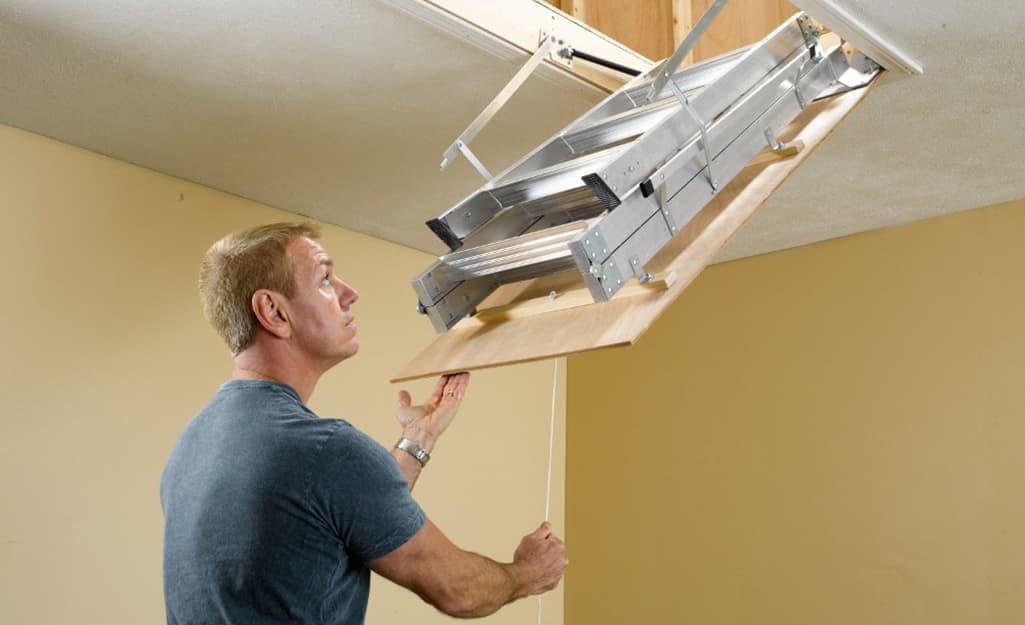 A man pulling down an attic ladder.