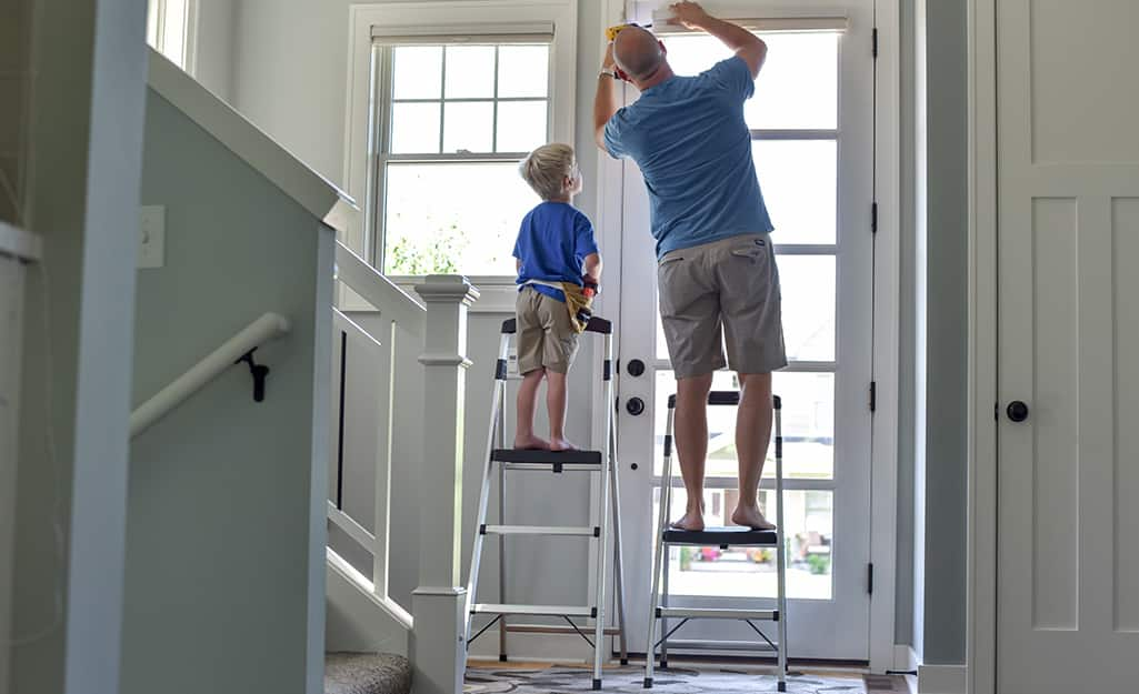 A father and a child each on a step ladder.