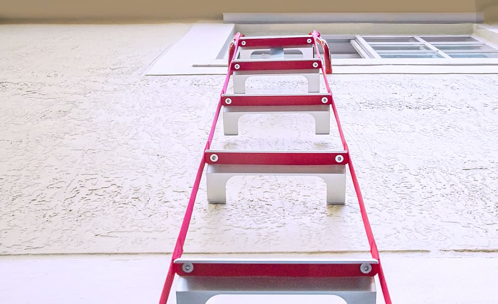 A fire escape ladder hanging from a second story window.