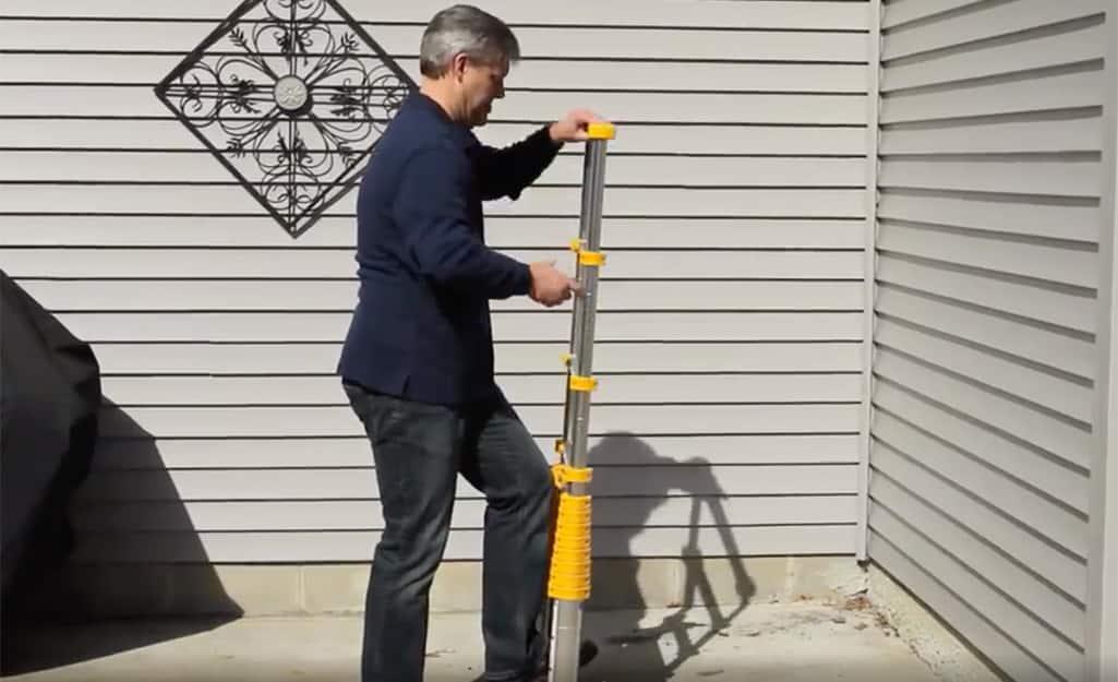 A man extending a telescoping ladder.