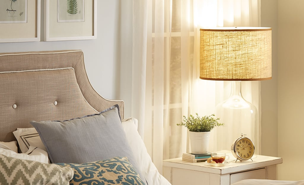A lamp with a fabric lamp shade on a night stand.