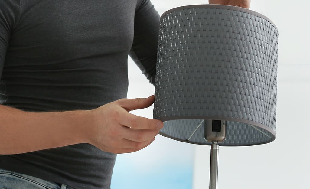 A person putting a lamp shade onto a lamp.