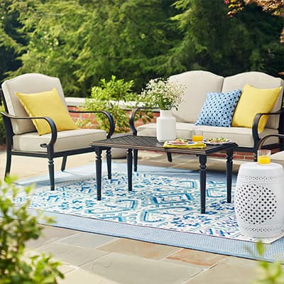 A blue patterned rug lays under a patio set.