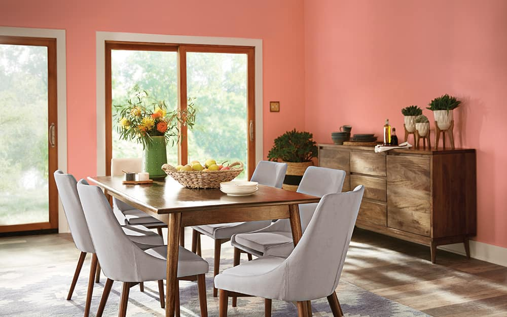 A dining room is painted in a melon paint with a matte finish.