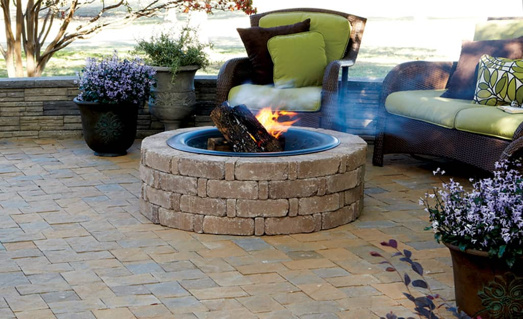 A firepit and patio made of paving stones with a chair and, love seat and pots of blooming flowers.