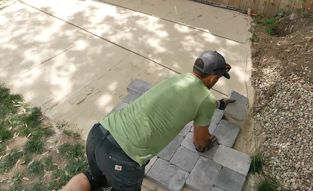 Someone installing pavers outdoors.