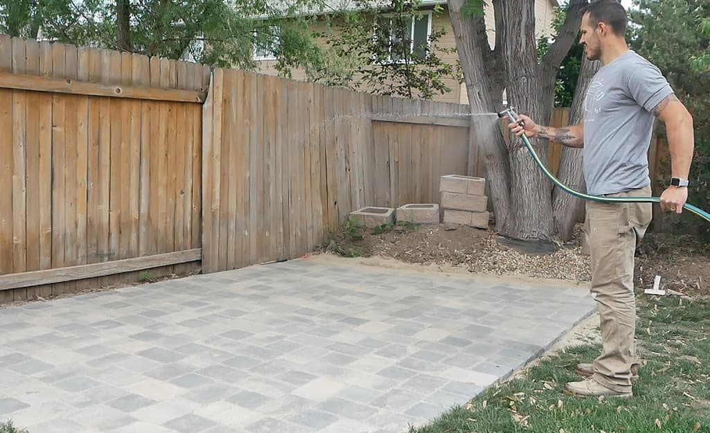 A man using a hose and spray nozzle to clean off a paver patio.