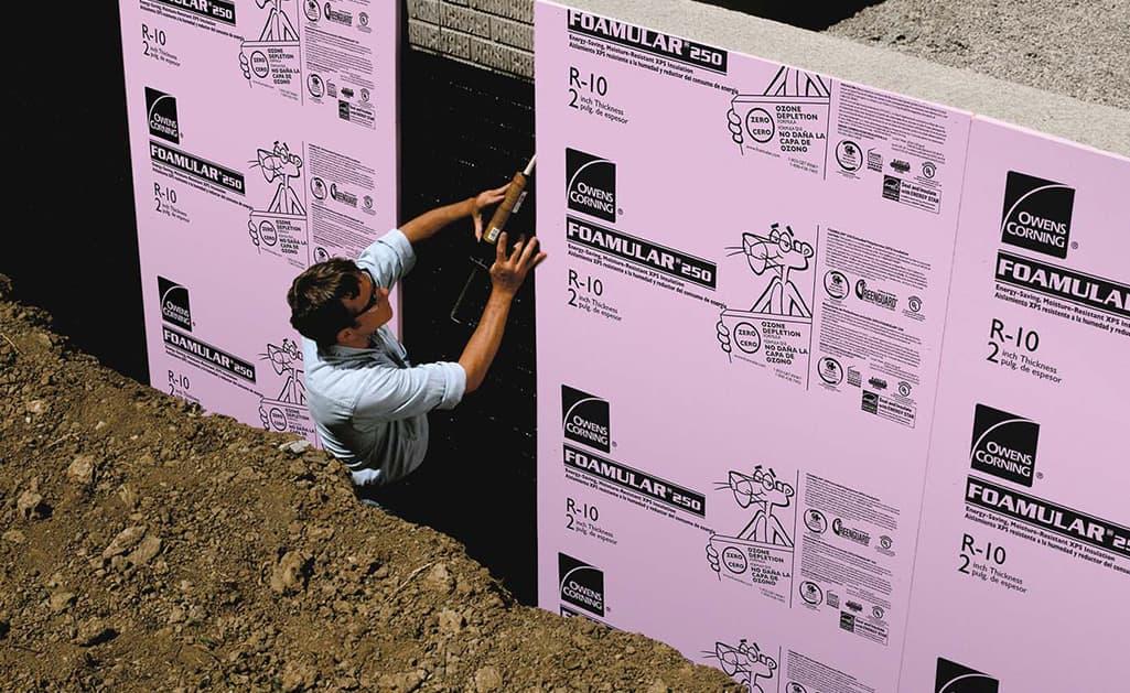 A man installing foamboard sheathing.