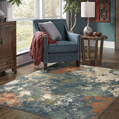 A colorful area rug under a blue easy chair in a living room.