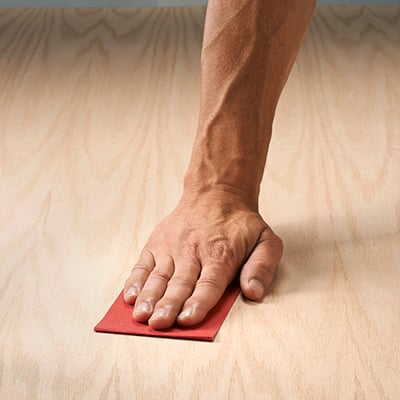 A person applies sandpaper to a wood surface.