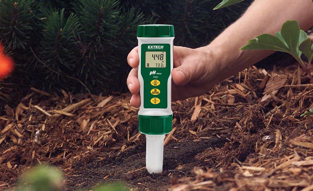 A person using a soil test kit.