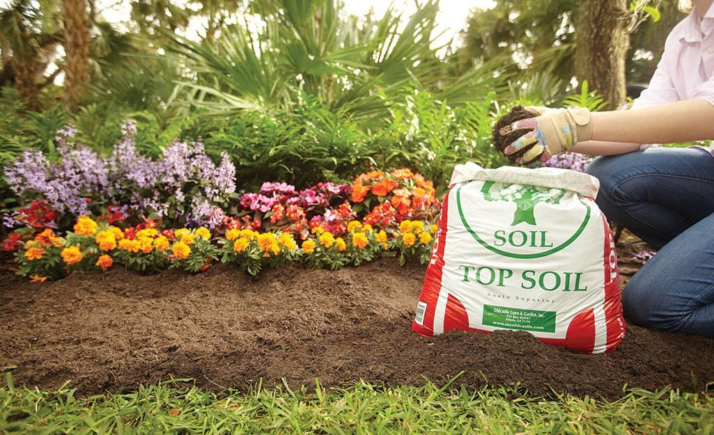A person adds topsoil to a garden.