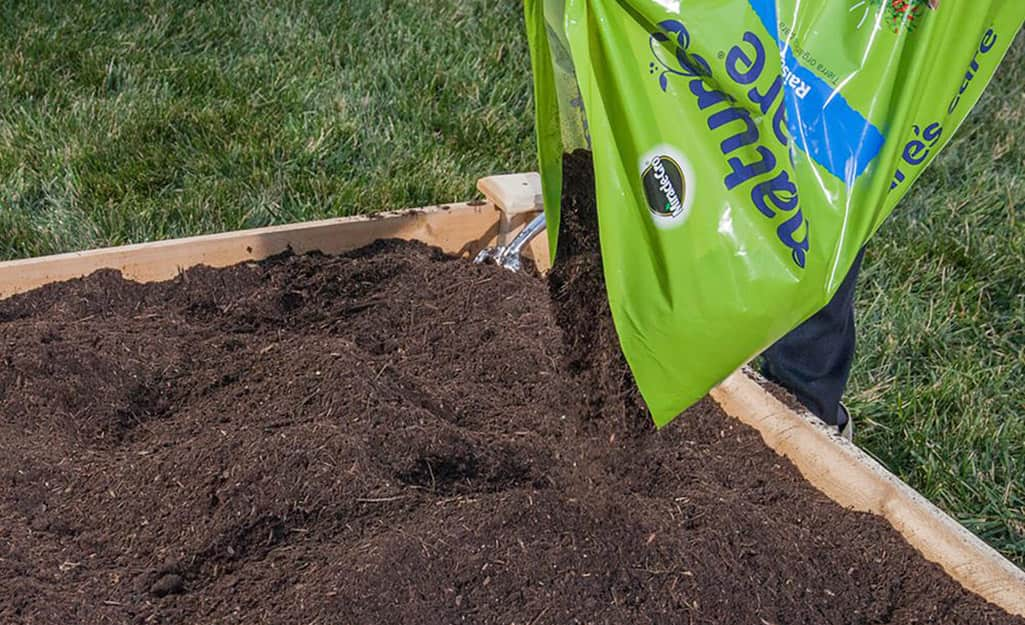 A person adds a bag of raised bed soil.