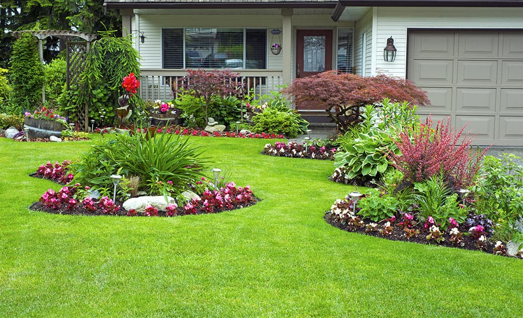 A vibrant green front lawn with neatly landscaped areas of flowers.