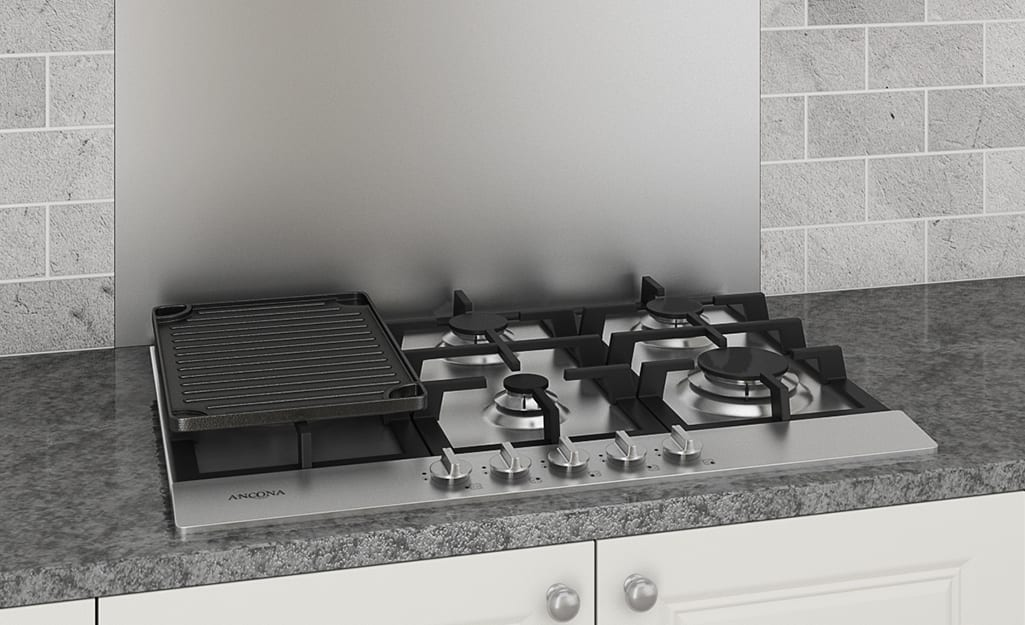 A gas stovetop with a grill accessory installed in a kitchen countertop.