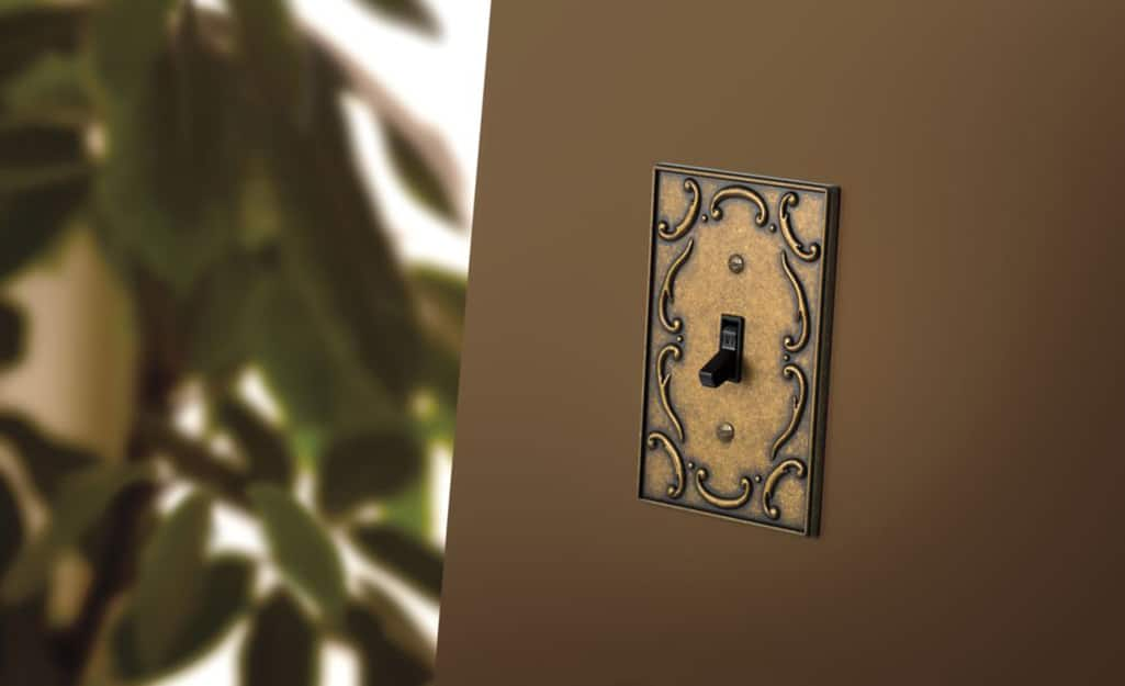 A toggle light switch with a decorative metal wall plate.