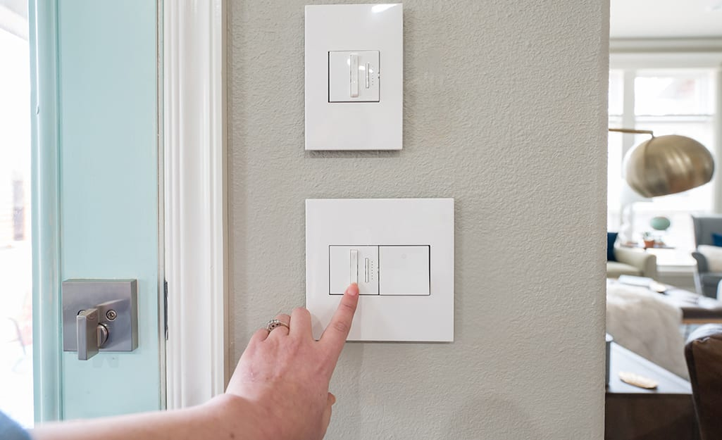 A person touching a single plate wall switch.