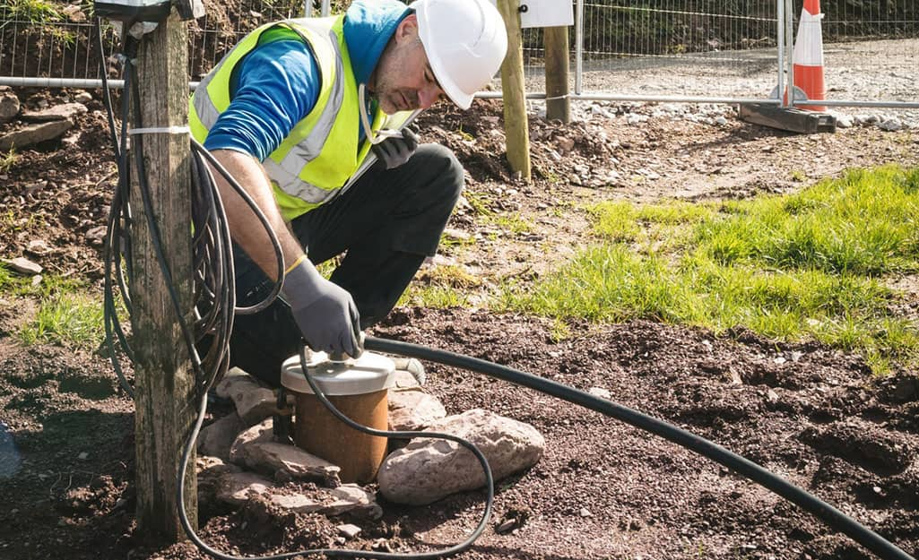 A man installing connections to a well pump casing.