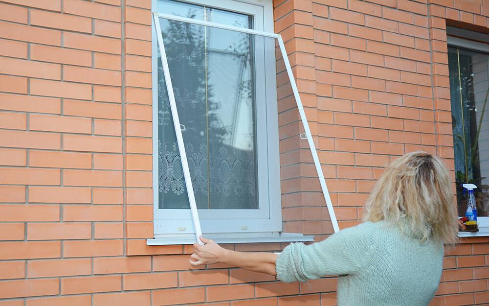 A woman putting a window screen in a window.