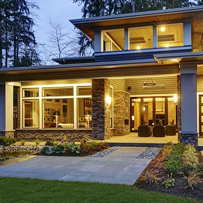 exterior shot of a modern home, well-lit from the inside and with a lot of windows