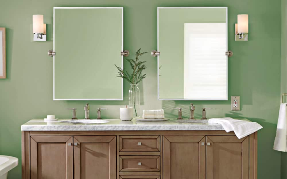 his and hers bathroom sinks featuring vanity lighting on each side of the mirror
