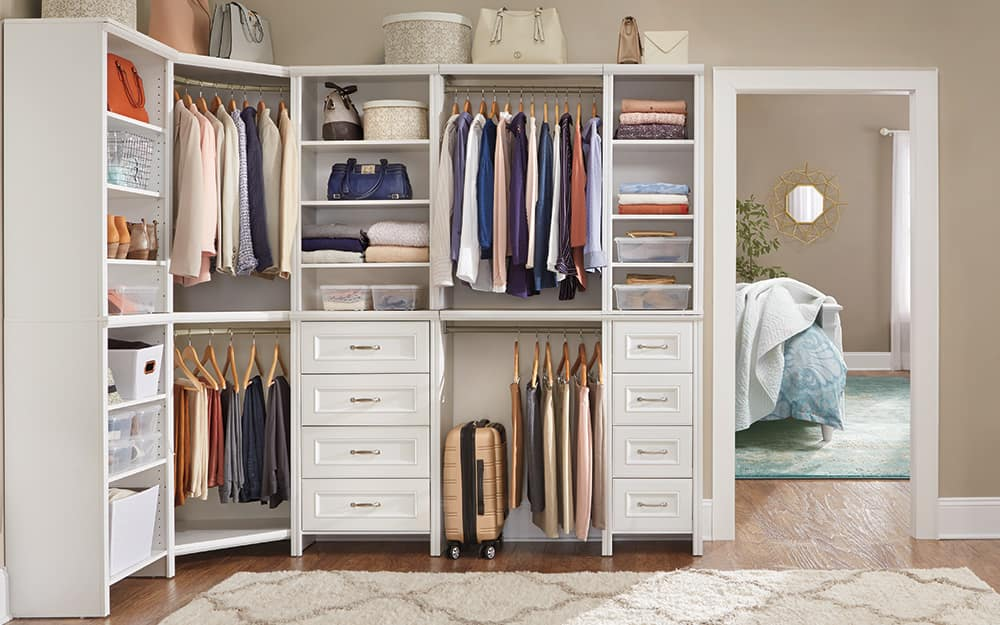 Walk-in closet with a complete closet system in white wood.