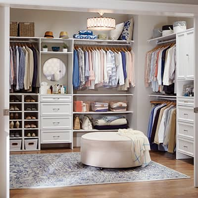 A well-organized walk-in closet with a wood closet system
