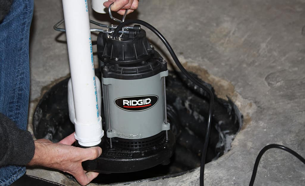 A submersible sump pump being placed in a basement drain.
