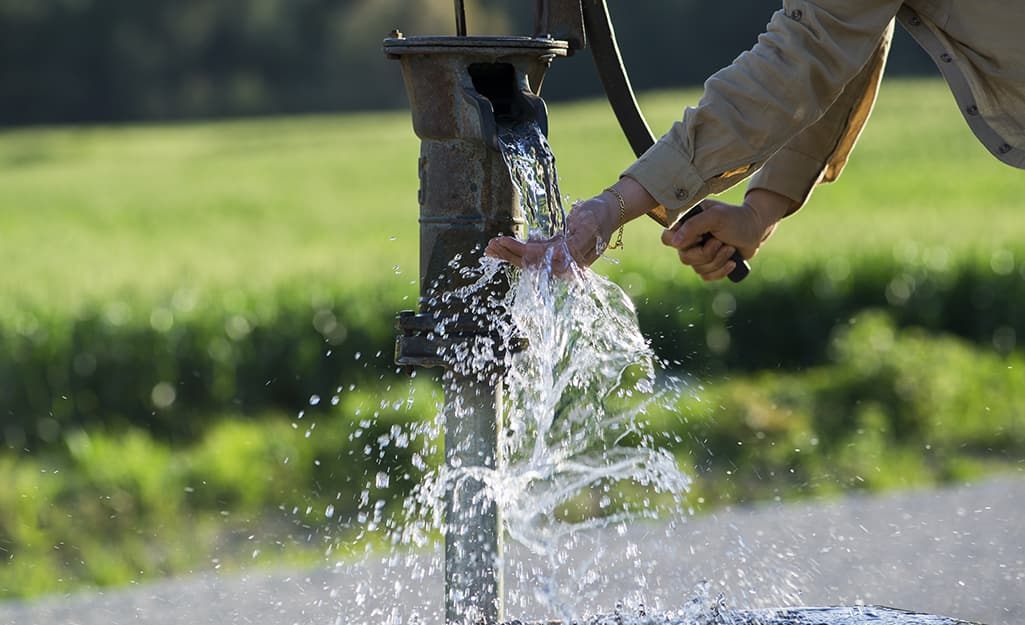Someone using a hand pump at a well.