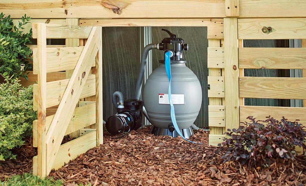 Pump inside a wood outdoor shed.