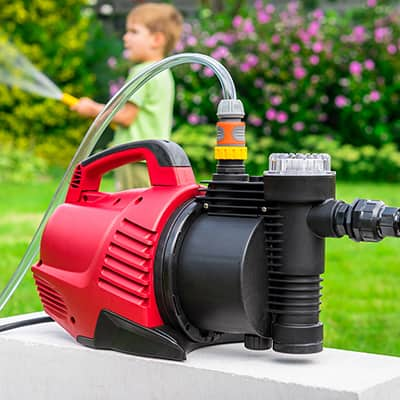 A water pump sitting in front of a child using a hose.