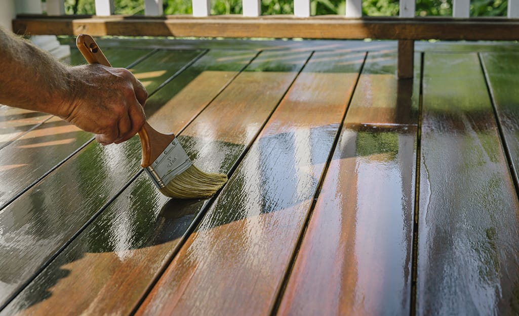 Person applying sealer to a wood deck.