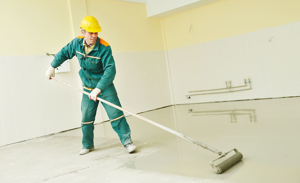 Person applying sealer to a basement.