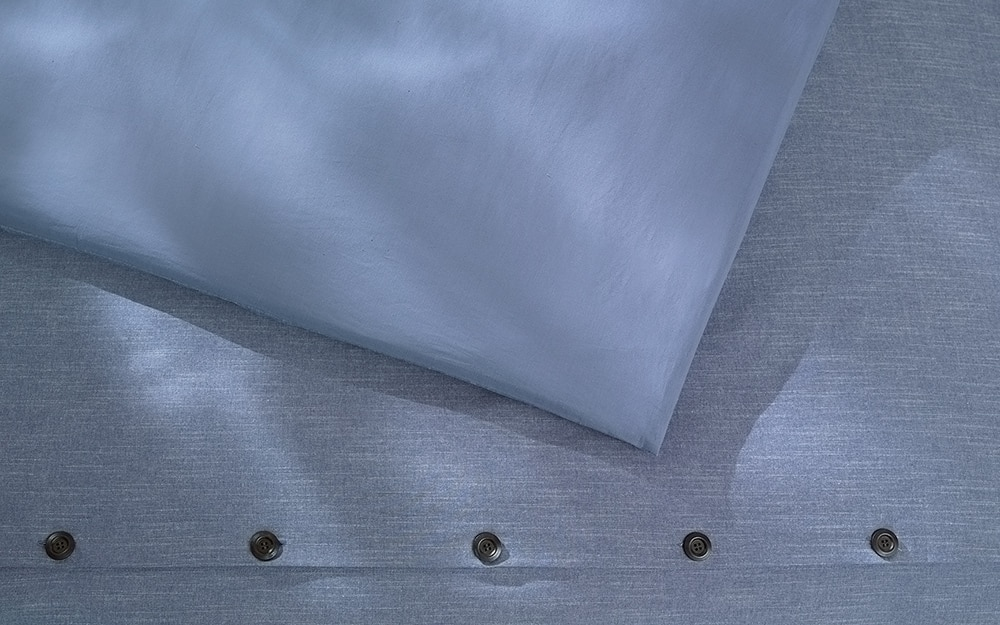 Blue duvet cover fastened with buttons.