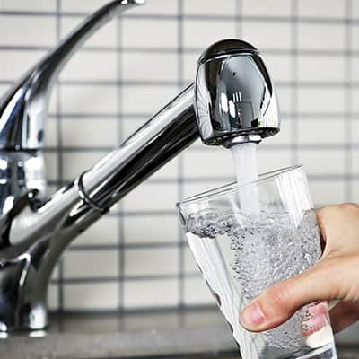 A person filling a glass with water from a kitchen faucet.