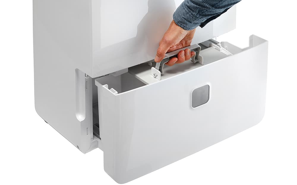 A person removes the drain tank of a 95-pint dehumidifier.