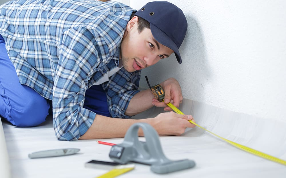 A person measures the size of a room with a tape measure.