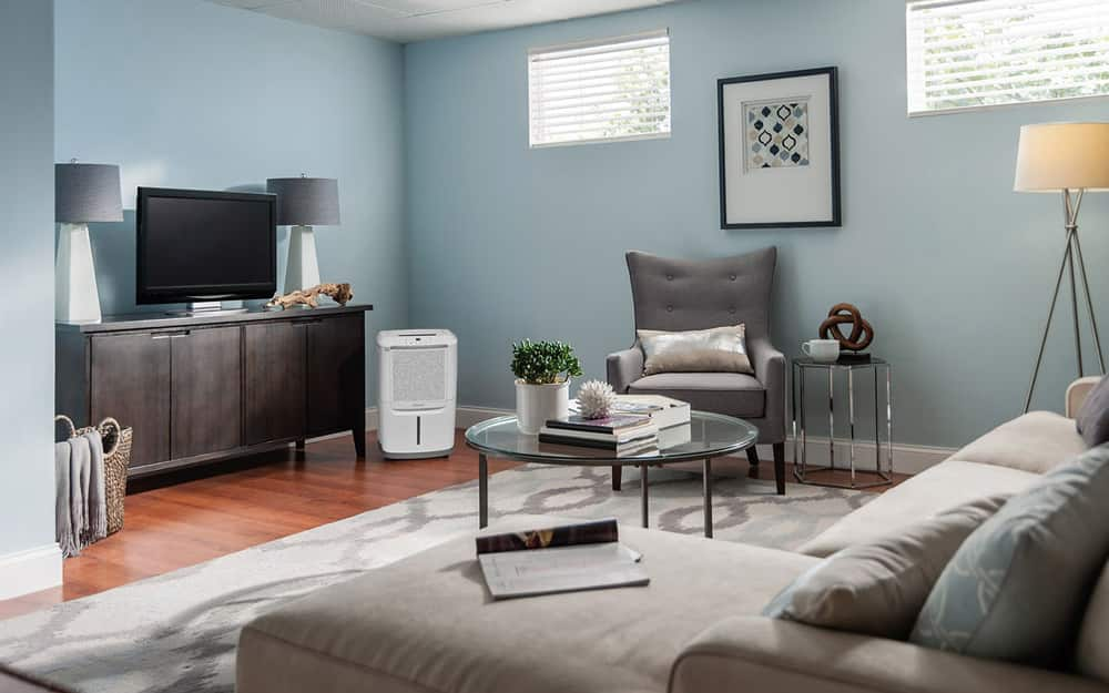 A 70-pint dehumidifier sits in the corner of a living room.