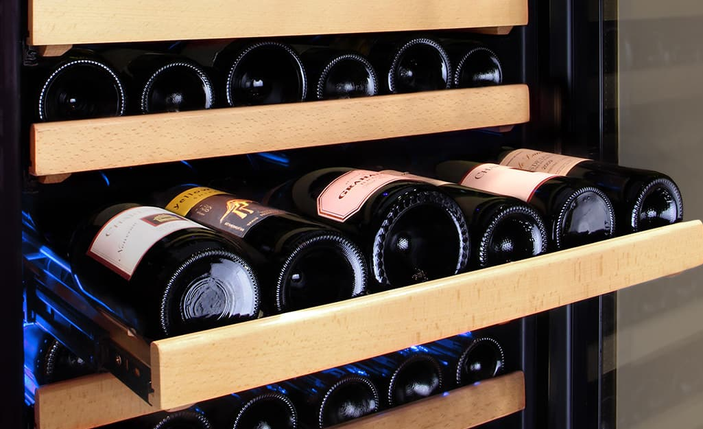Six bottles of wine laying on a shelf inside a wine cooler.