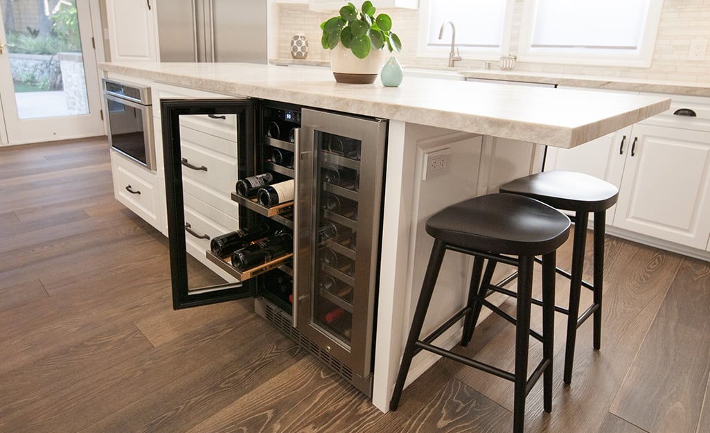 A stainless steel built-in wine cooler installed in a kitchen island.