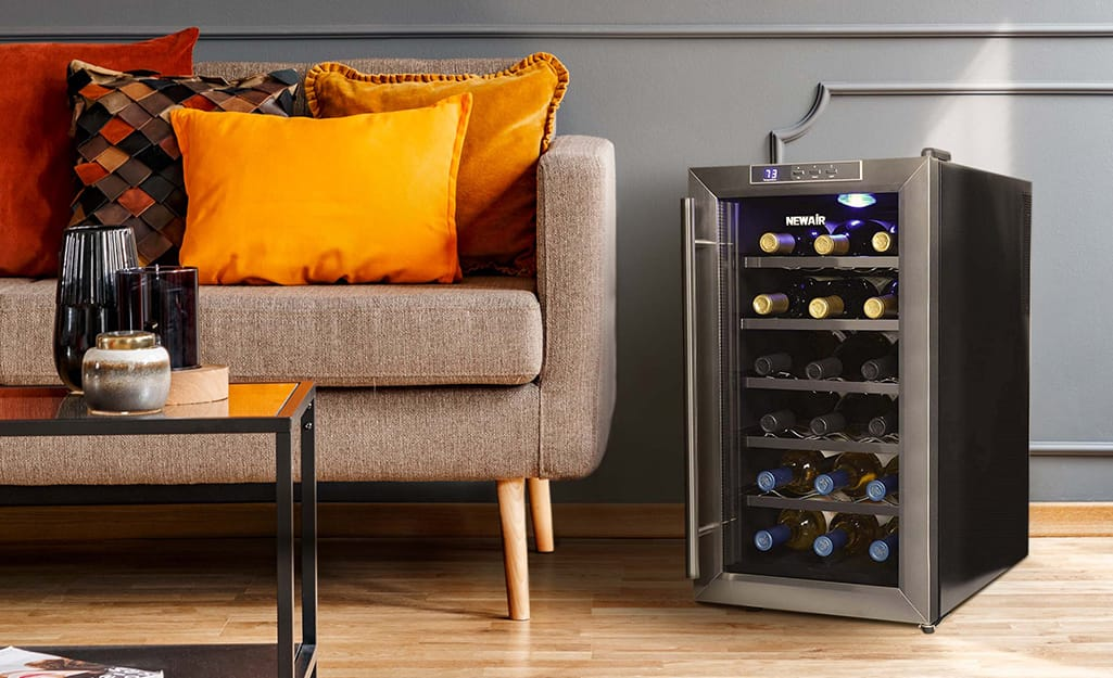 A free standing wine cooler sits near a sofa.